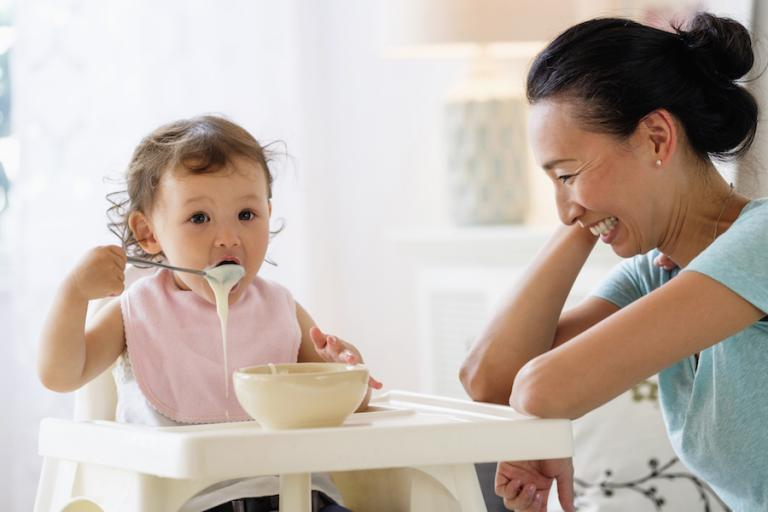 Baby eating cereal in highchair