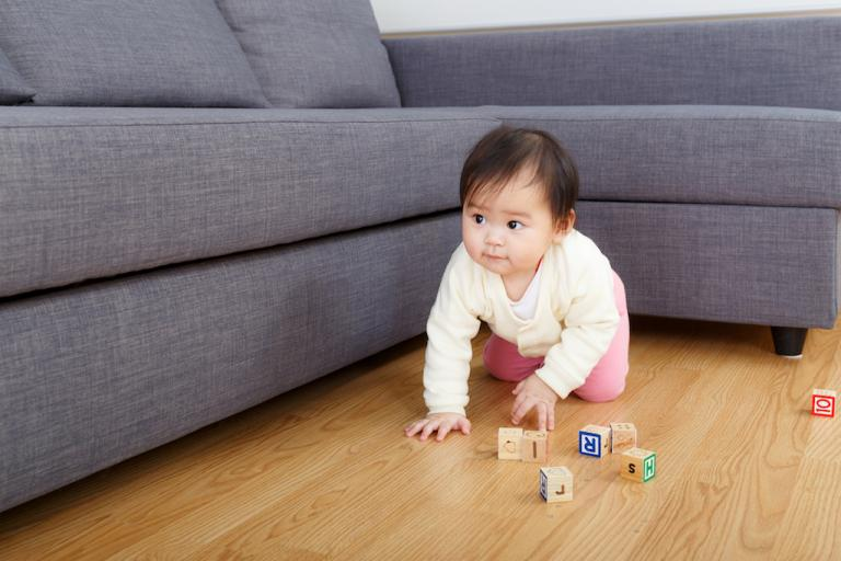 Baby playing with blocks on a wood floor