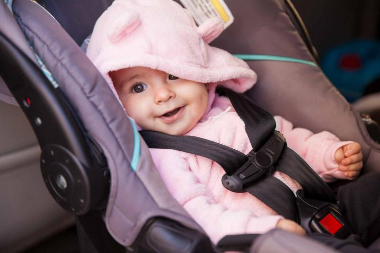 happy baby sitting in car seat
