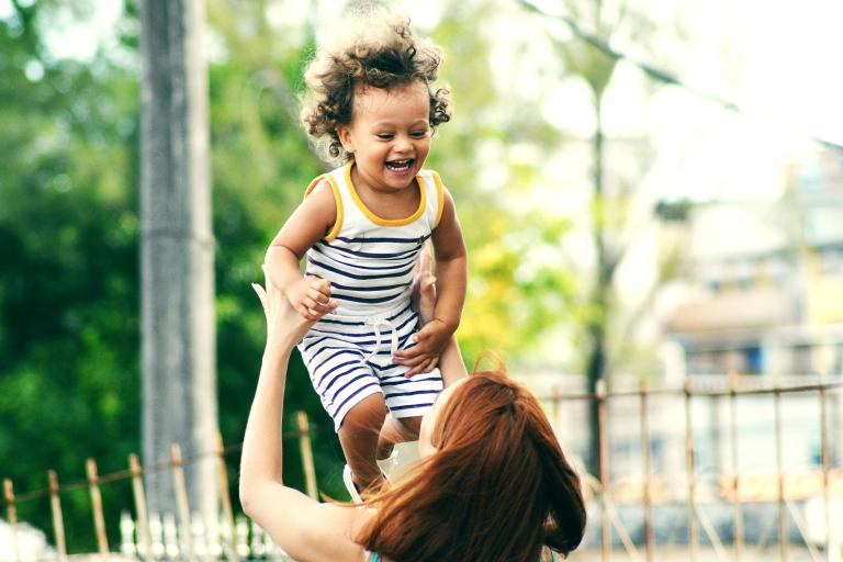 Photo of woman lifting happy child during daytime