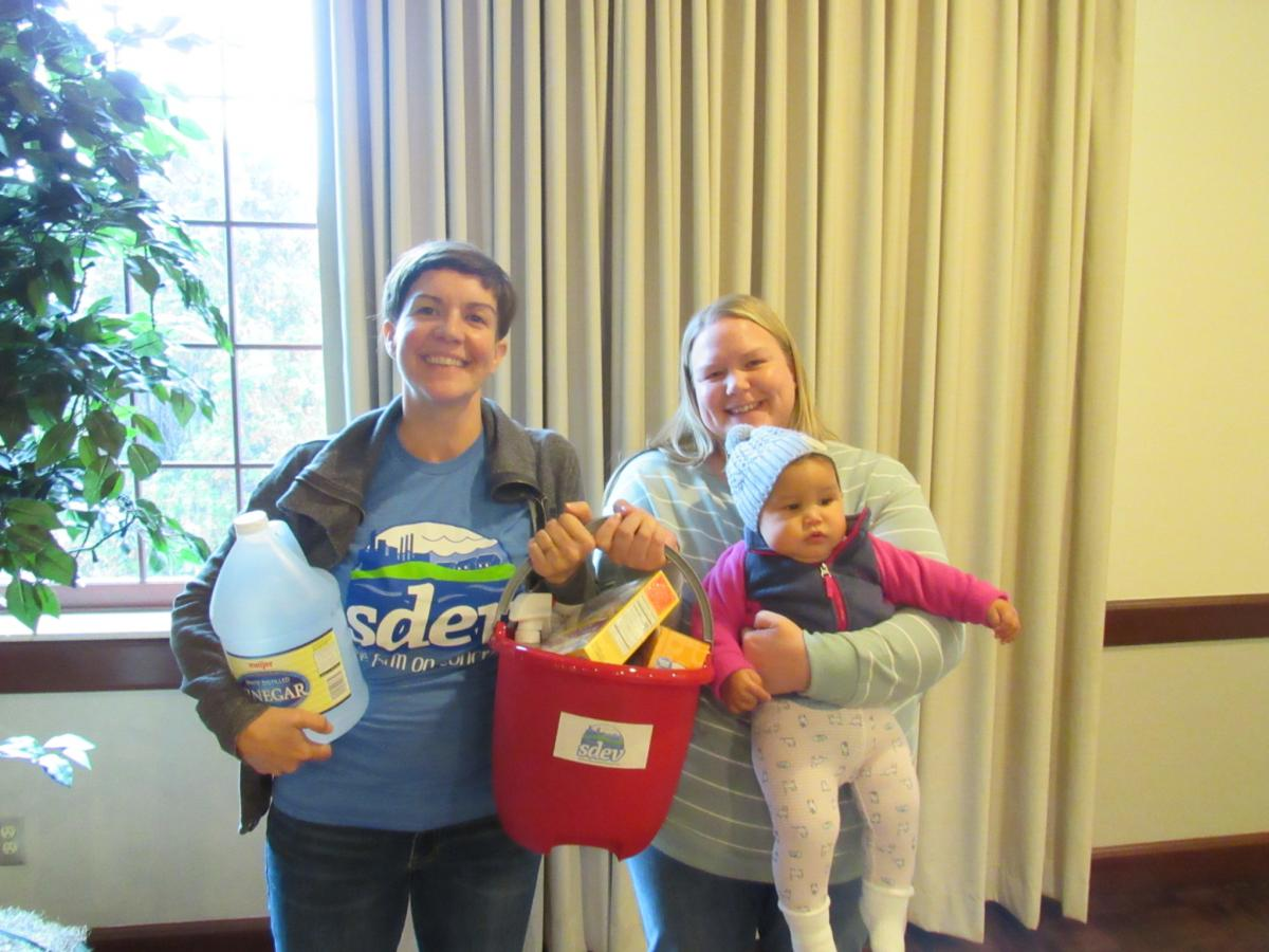 Two people holding a baby and a bucket of toxic-free supplies at SDEV event in Dearborn Michigan