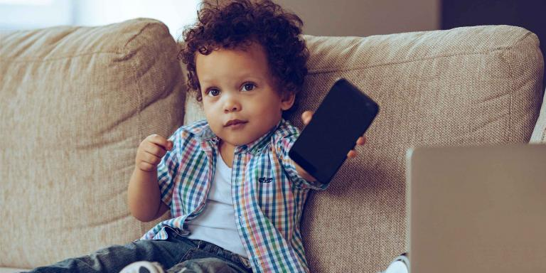 Child sitting on couch holding a cell phone