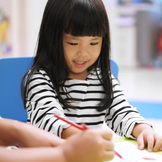 young girl drawing in classroom